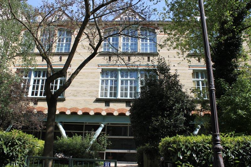 Façade de l'Ecole Sacré-Coeur d'Hector Guimard avec ses assises en brique rouge et ocres et ses colonnes vertes en V.