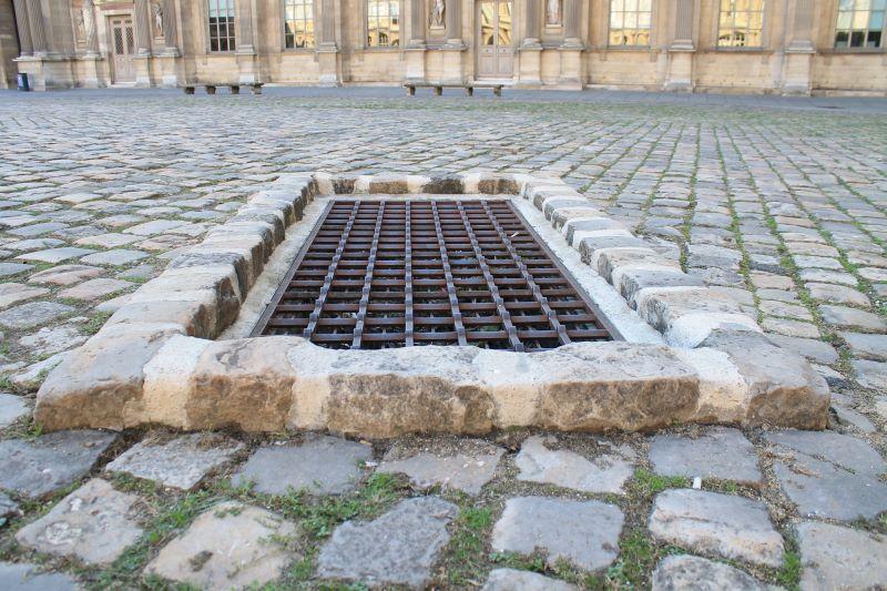 Ouverture d'une citerne rectangulaire visible dans la Cour Carrée du Louvre